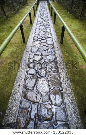 Wet paved footpath between bamboo railings in the formal garden at Koto-in, a sub temple of Daitoku-ji in Nara , Japan