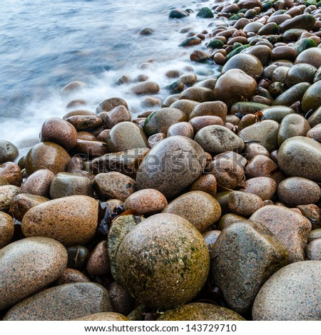 Wet pebbles on beach with blurred ocean, Maine, USA
