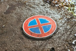 Wet red road sign as sewerage cover, red cross over blue metal circle. dirty, grime, water on top. Green moss on concrete, small rocks, puddle, rusted metal frame, sun, spring day