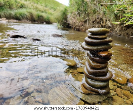 Wet river pebbles stacked on top of each other on the river side. Stone pile in fresh water stream.  Stockfoto ©