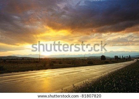 Wet road after rain and sunset over fields