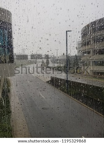 Wet road through airport window with rain drizzling down