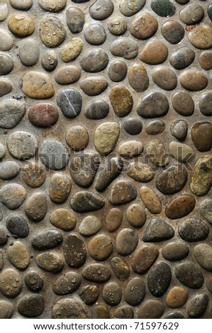 Wet round stone rock texture with tiny water drops on them and dramatic lighting.
