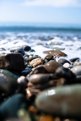 Wet sea stones on the sea line, blue sea behind, sunny day, blue sky, shallow focus