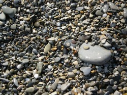 Wet shingle on a beach. Sea pebbles. Background of pebbles. Multicolored pebbles. Colorful beach stones. Glare, beach. summer, holidays, vacation, travel, nature, romantic getaway, tourism concept