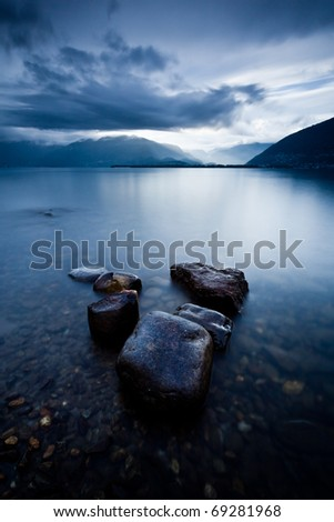 wet stones by lake shore under clearing storm light forming a V shape