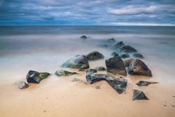 Wet stones on the sandy lake shore. Long exposure