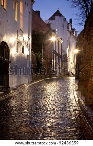 Wet street with old houses at night in Dutch city called Nijmegen.
