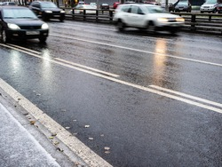 wet surface of city road and blurred in motion cars on autumn evening