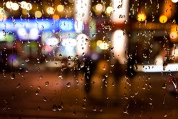 Wet the window with the background of the autumn night city