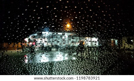 Wet the window with the background of the autumn night city. Selective focus.  #1198783921