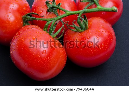 Wet tomatoes isolated on black, tomatoes covered drops