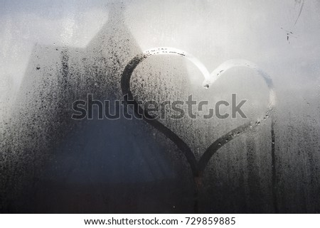 wet window with heart shaped hand drawning #729859885