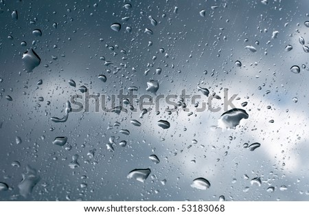 Wet window with rain drops and a cloudy stormy sky outside