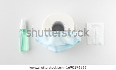 Wet wipe Alcohol hand sanitizer spray Surgical mask with rubber ear straps. Typical 3-ply surgical mask to cover the mouth and nose. Toilet paper. White Background. Flat lay Top view