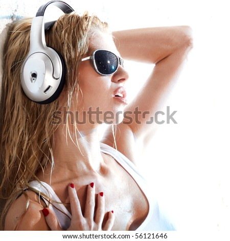 Wet woman in white shirt and sunglasses listening for the music using headphones