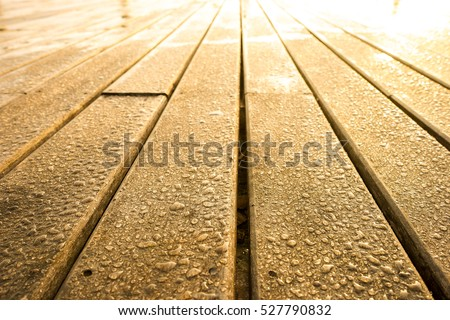 Wet wooden background with warm light