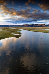 Wetlands in California at Sunset.  River leads off into the distance towards mountain range with colorful reflections in water.