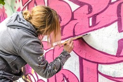 WETZLAR, GERMANY - 23.05.2021: Young female Artist doing artificial typography colorful graffiti senic on house facade in WETZLAR; GERMANY