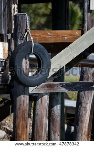 Wharf side dock with black rubber tire awaits boats