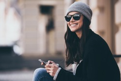 What a beautiful day! Side view of beautiful young woman in sunglasses using her smartphone and looking away with smile while sitting outdoors