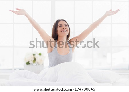 What a great morning! Cheerful young woman sitting in bed and stretching out while covered with blanket