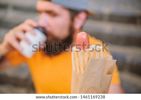 What a sausage. Hipster drinking coffee with hotdog snack on stairs outdoor. Caucasian guy enjoying snack on street. Bearded man snacking with unhealthy sandwich snack. Snack and food.