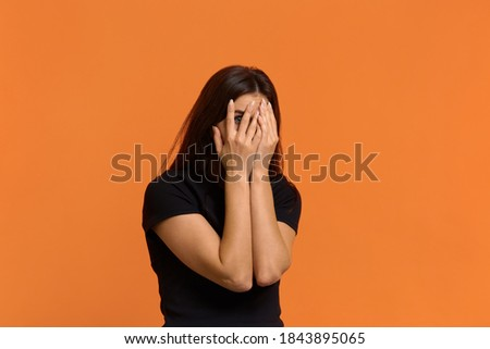 what are these horrors. Scared caucasian woman in black t-shirt peeps through fingers, hides face with hands, afraids of something terrible. Isolated over an orange background Stock photo ©