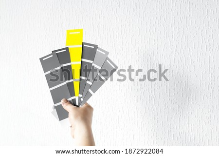 What color in 2021 will you choose? Trendy pantone colors on palette - Illuminating Yellow and Ultimate Gray. Holding color swatch guide in hand