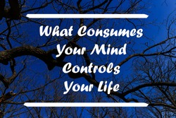 What Consumes Your Mind Controls Your Life written against a blue sky and bare branches. Inspirational motivation quote.