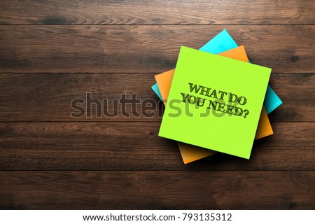 What Do You Need, the phrase is written on multi-colored stickers, on a brown wooden background. Business concept, strategy, plan, planning. Foto stock ©