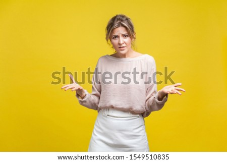 What do you want? Portrait of irritated young woman with fair hair in casual blouse standing with raised arms, looking at camera, demanding answer. indoor studio shot isolated on yellow background Foto stock ©