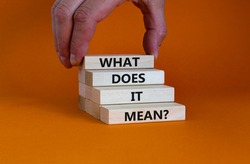 What does it mean symbol. Concept words 'what does it mean' on wooden blocks. Beautiful orange background. Businessman hand. Business and what does it mean concept. Copy space.