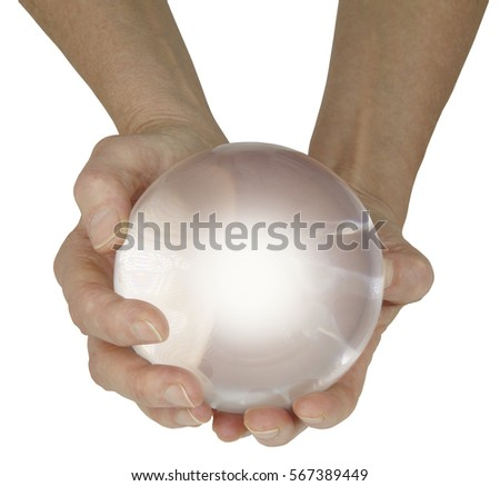 What does the future hold - female fortune teller with large crystal ball held in cupped hands with a soft white center isolated on a white background #567389449