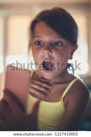 What happened? Shocked little girl  using smart phone. Copy space. Close up. Copy space. Focus on child. #1227433003