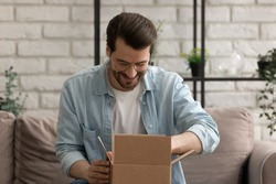 What is inside. Curious millennial male sitting on couch at home opening small cardboard box received by mail. Interested young man unpacking shipment delivered to addressee by express courier service