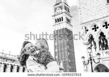 What makes Venice even more magical are kisses... Here, a little girl gives her mother a kiss on the cheek while her mother holds. The mother is laughing and delighted. #1098107816