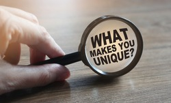 What makes you unique question under magnifying glass. Career business concept.