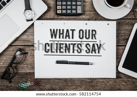 What Our Clients Say statement on paper note pad. Office desk with electronic devices and computer, wood table from above, concept image for blog title or header image. Aged vintage color look. #582114754