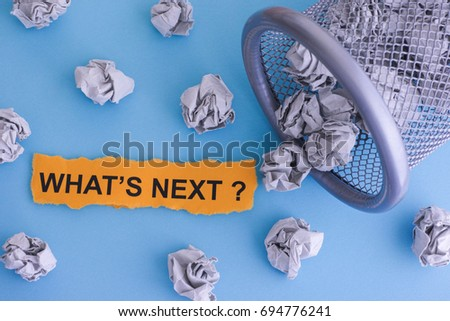 What's next? Grey crumpled paper balls rolling out of a trash can. Close up. Concept image.