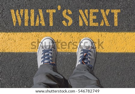 WHAT`S NEXT print with sneakers on asphalt road, top view.