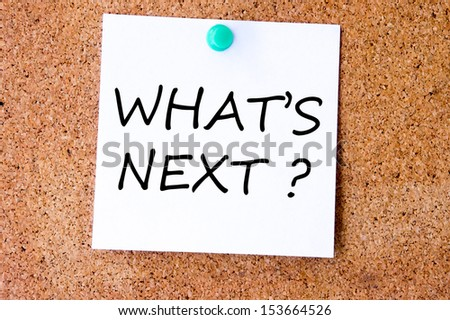 What's Next, written on an white sticky note pinned on a cork bulletin board.
