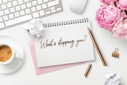 What's stopping you? Feminine workspace with bunch of peonies in a vase, computer, writing supplies, paper balls and a cup of coffee and hand-written quote on a white desk. Business concept. Flat lay.