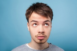 What's with my hair. Closeup portrait of young brunette man with small beard and mustache in casual sweater looking up with inquiring gaze, dissatisfied with messy fringe hairstyle, studio shot