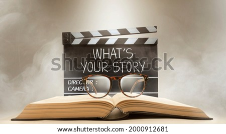 what's your story, text title on the film slate, and eyeglasses on top of the old book Сток-фото ©