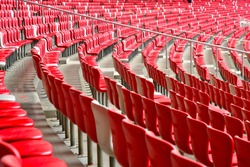 What seems as endless rows of red plastic seats in a soccer stadium that is otherwise completely empty