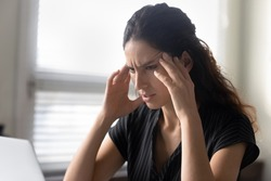 What should I do. Stressed latina woman sit by pc rub temples feel information overload unable to focus attention on work. Anxious young female try to remember important thing solve unexpected problem