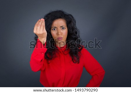 What the hell are you talking about. Shot of frustrated young European woman gesturing with raised hand doing Italian gesture, frowning, being displeased and confused with dumb question.