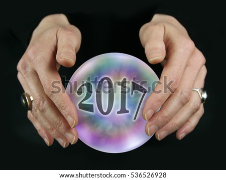 What will 2017 bring - Crystal Ball reading showing a 2017 inside a colorful translucent crystal ball between female hovering hands on a black background #536526928