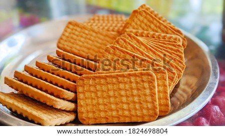 Wheat biscuits in the steel plate with blury background. Indian biscuits popularly known as Chai-biscuit in India Photo stock ©